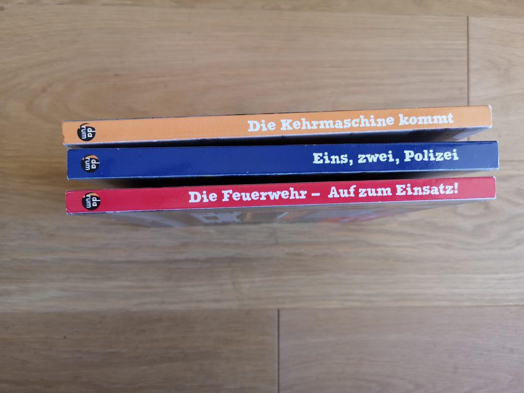 Drei Buchrücken aus dem Darum Verlag - die Kehrmaschine, die Polizei, die Feuerwehr